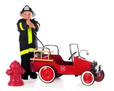 Boy-standing-by-fire-truck-ride-on-toy