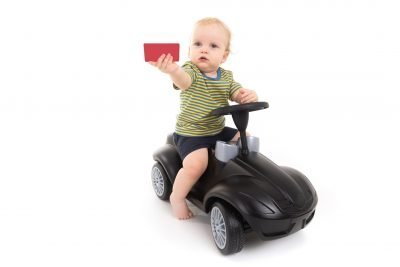 This is an image of a baby boy on a black plastic ride on toy