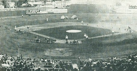 This is an image of the First known indoor motocross event on a baseball field
