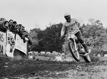 Joel Robert taking on a turn in an MX race with a crowd watching from the side