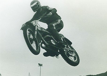 Man at MX race doing a massive air jump on his bike