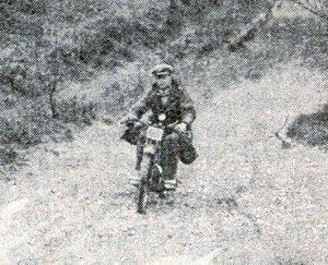 Man riding motocross bike through a field