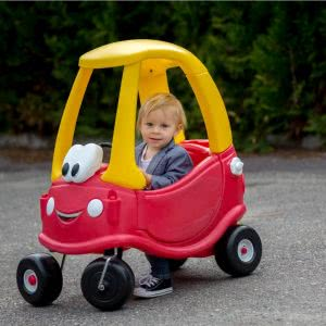 This is an image of a little boy driving a ride on toy car