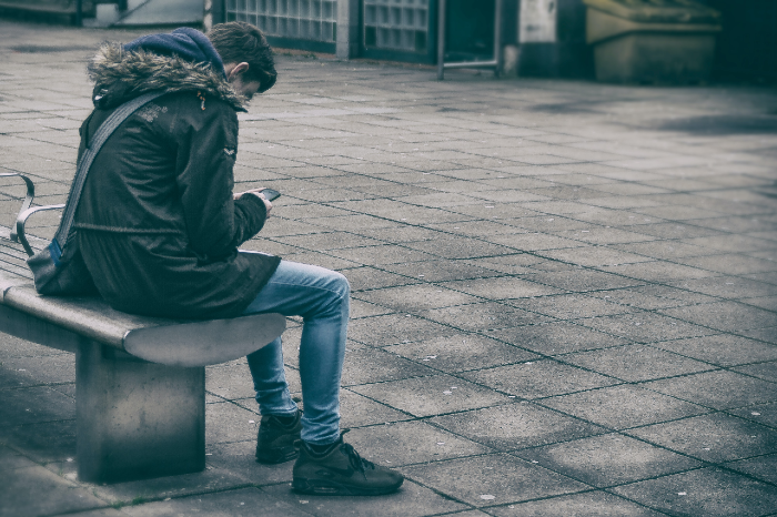 This is an image of a boy looking at his phone while sitting on a bench outside